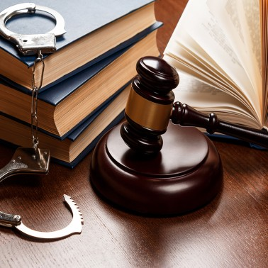 Gavel, books and handcuffs on wooden table