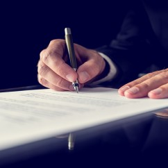Retro image of lawyer signing important legal document on black desk. Over black background.